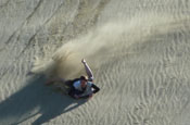 Riding boogie board on sand dunes